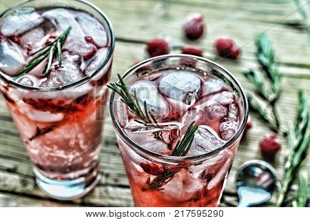 Domestic cocktail with ice and rosemary. Alcohol cocktail or Fruity cocktail drink decorated with frozen or fresh raspberry, strawberry, rosemary, ice and soda.