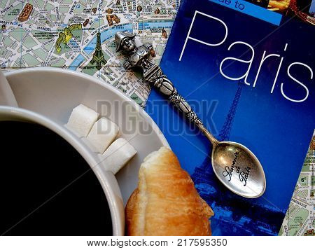 Symbols of Paris and France in flat layout or background. Cup of coffee with croissants and sugar, tea spoon, guide to Paris with map. Vacation tour or tourist journey to Europe. Editorial only. The map used in composition, has been gotten from open sourc