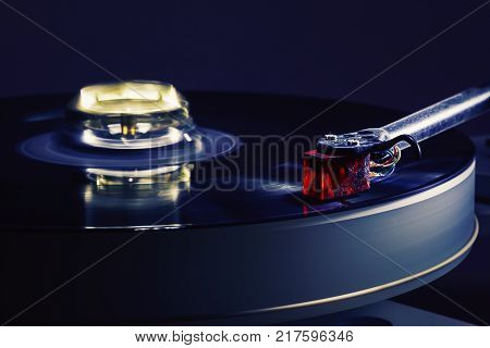 Details of modern gramophone in work dark ambient accentuated shapes with illumination.