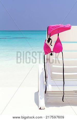 Pink female swimsuit hanging on white beach chaise lounge with sea background. Travel destination card, nobody