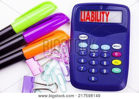 Writing word Liability text in the office with surroundings such as marker, pen writing on calculator. Business concept for Accountability Legal Blame Risk white background with space