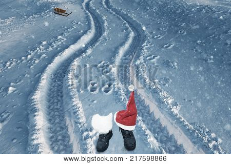 boots with white felt and christmas hat on fresh snow