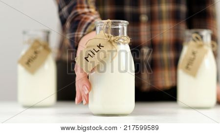 Woman offering milk. Quality dairy products. Healthy lifestyle. Calcium and vitamin D
