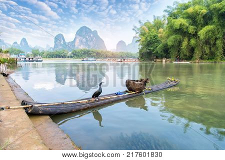 Cormorant standing on a bamboo raft on the guilin li river