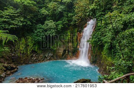 Top view long exposure of celestial blue waterfall and pond in volcan tenorio national park