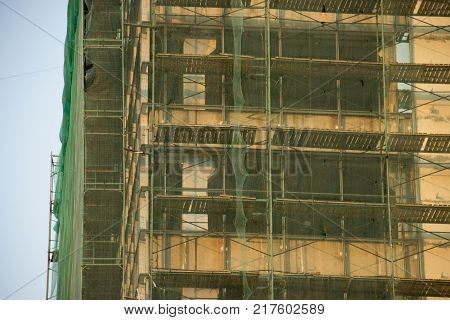 Scaffold on a old house for renovation. Ocher beige green and blue background. Reconstruction of buildings and structures. Elements of rusted scaffold with green protection mesh.