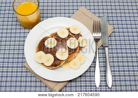 Banana pancakes with chocolate and orange juice Children's breakfast a stack of pancakes with banana and chocolate spread