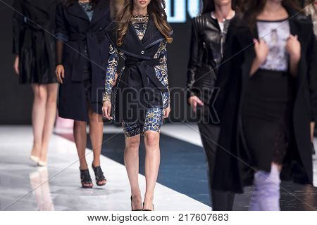 Sofia, Bulgaria - 28 September 2017: Female model walks the runway in white dress during a Fashion Show. Fashion catwalk event showing new collection of clothes. White dress.