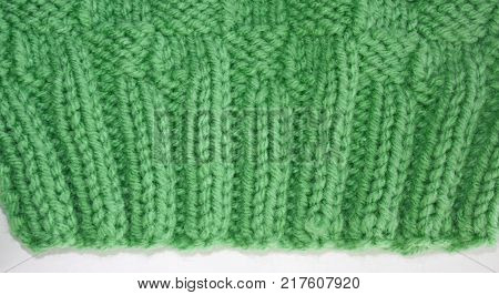 Close up of the knitted Rib Stitch.  Knit two, purl two, knit two, purl two in a pretty green color wool.  Then knitted in a Basket Weave stitch