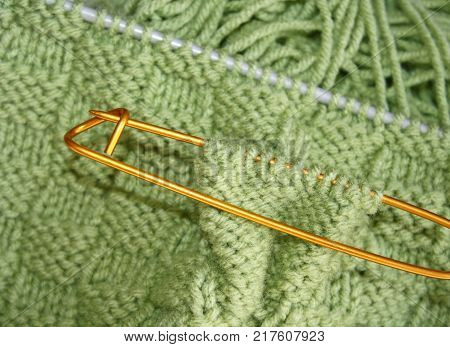 Basket weave pattern knitted on knitting needles in sage green color wool.   Stitch holder in place marking off extra stitches to be knit later