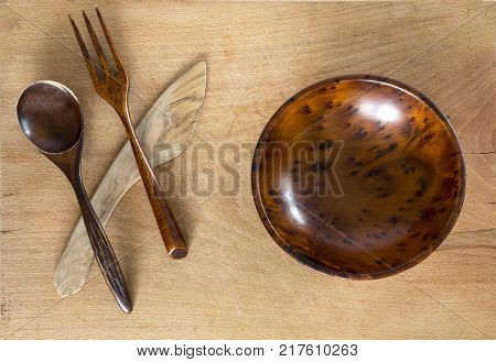 Wooden bowl spoon fork and knife on a wooden background from above. Studio shot. Kitchen utensil.
