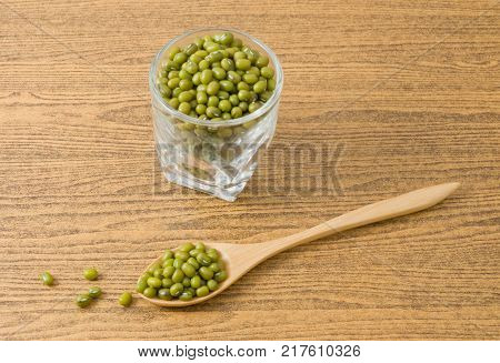 Cuisine and Food Raw and Uncooked Mung Dried Beans in Wooden Spoon and Tumbler on Wooden Table.