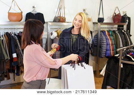 young woman paying to shop assistant by credit card and receiving shopping bags in store. Credit card shopping concept