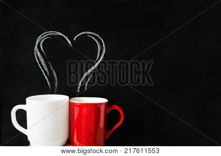 Two cups red and white with chalk-drawn smoke in the form of a heart on the blackboard. Pair of cups with a chalk heart with copy space. Breakfast on Valentine's Day. Love coffee and romance concept