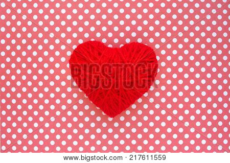 Heart of red threads on a background of cloth in polka dots. Red heart shape made from wool on textile red and white polka dots background. Yarn heart shape symbol. Concept of love Valentines day