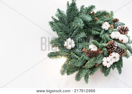 gifts of nature, traditions, christmas concept. small fuzzy wreath crafted of fresh fir branches and carefully embellished with cotton flowers and pinecones