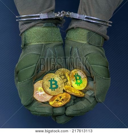 Arrested hareks handcuffs hands hold golden bitcoins.