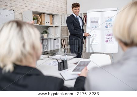 Portrait of smiling young businessman standing by whiteboard giving presentation of statistics report on marketing and finance to group of executives