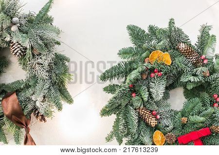 interior design, christmas, winter concept. fuzzy branches of conifer tree weaved into tidy circle with ribbons and bow, with red berries and pinecones, and even dried fruits
