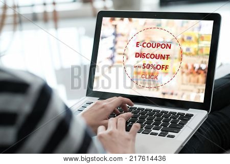 Woman entering the discount coupon code on laptop computer to get the grocery shopping on line promotion on line shopping digital marketing business and technology lifestyle concept