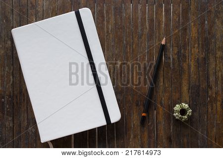 White cover notebook with black pencil on rustic wooden table flat lay photo. Closed notebook flat lay photo. Sketchbook and pencil table top view. Art supply banner template. Artistic travel mockup