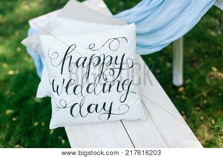 wedding, decor, gardening concept. original idea of garden decoration for nuptial in form of tidy little cushions in white and grey colours with interesting print of greeting words