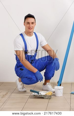 A European male painter in blue uniform, squatting near a pallet and jars of paint. Indoor in the house.