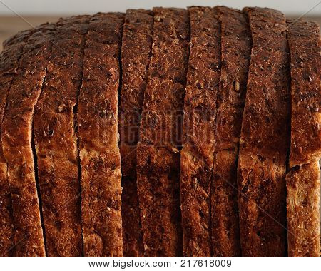 A loaf of whole wheat bread displayed on a wooden table