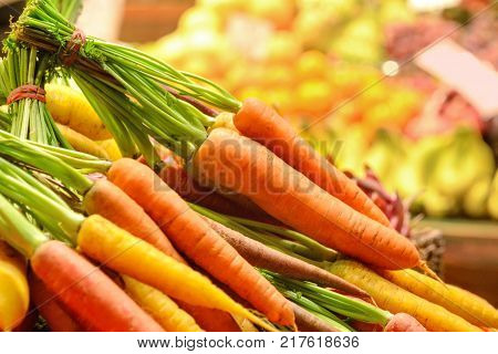 Fresh colorful organic sweet carrots on wooden counter of farmer's market. Background of fresh fruits and vegetables.