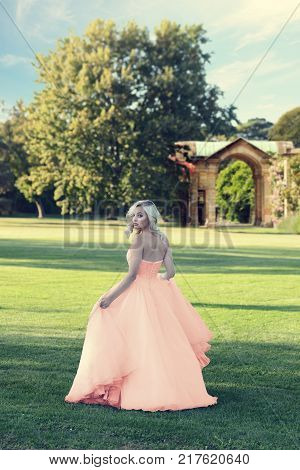 blonde woman in peach color tulle ball dress walking in formal garden