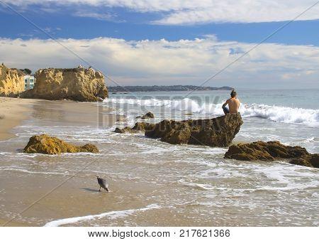 Man sitting on rock gazes out to sea in Malibu, California