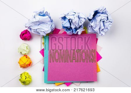 Writing text showing Nominations written on sticky note in office with screw paper balls. Business concept for Election Nominate Nomination on white isolated background.