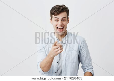Advertising concept. Excited cheerful european man wearing light blue shirt raising eyebrows and exclaiming, pointing index fingers at camera, choosing you, motivating and attracting customers.