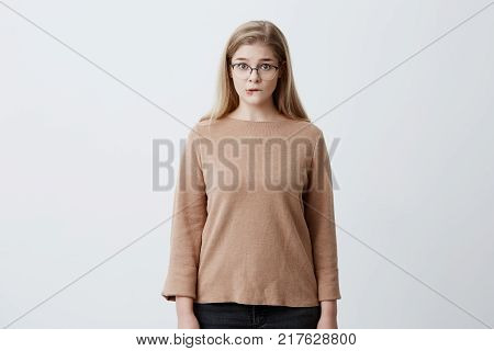 Puzzled pretty woman wearing eyeglasses with straight blonde hair biting her lower lip looking with surprise into camera. Human face expressions and emotions. European girl shocked posing against studio wall