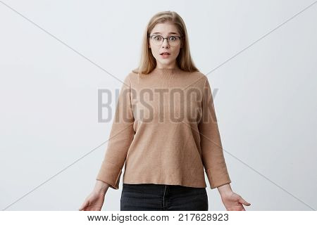 Stupefied shocked young woman looks with shocked expression at camera, with bugged eyes, astonished to hear shocking news. Caucasian female in eyewear has puzzled look, isolated against gray background