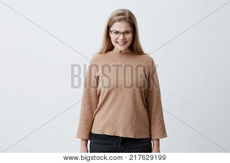Portrait of angry female wearing casual clothing and stylish eyeglasses, keeps teeth clenched, frowns face in dissatisfaction, irritated because of much duties. Furious blonde girl in anger
