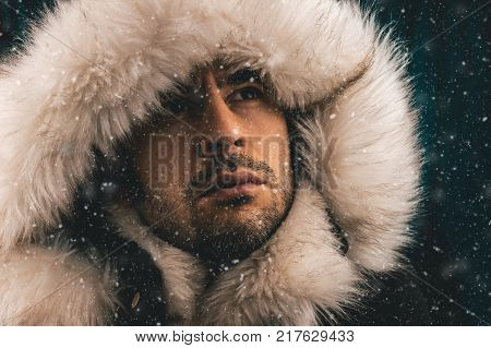 Close up portrait of a white man dressed with an eskimo jacket in the snow looking up