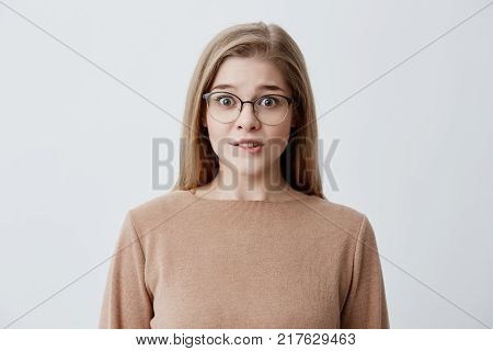 Young blonde female having worried look biting her lower lip nervously looking with anxious eyes at camera through stylish eyewear isolated against gray background. Cute woman in loose brown sweater with nervous expression