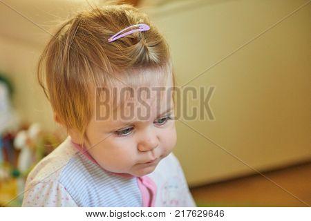 Baby girl blonde in children's room looking away