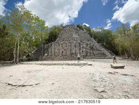 Coba Mexico - May 25 2016: Tourists climbing stone Temple at Coba Yucatan Mexico May 25 2016
