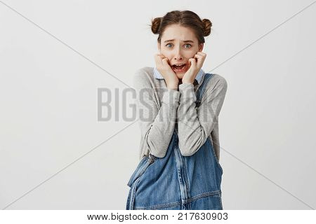 Young frightened woman in casual holding her hands on cheeks and screaming in panic. Schoolgirl being terrified after watching horror movie. Emotions concept