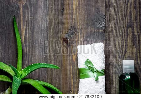Organic aloe vera cosmetics. Aloe vera leafs, glass of aloe vera juice on wooden table background top view.