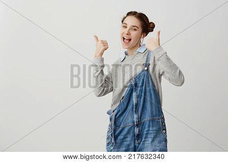 Girl 20s in denim being happy gesturing thumbs up over white wall. Female infantile writer celebrating success of her new book listening it in electronic version via earphones. Technics concept
