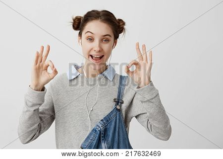 Closeup picture of appealing woman showing alright with fingers enjoying music from headphones. Adult female being in good mood after listening audiobook with her smartphone. Body language