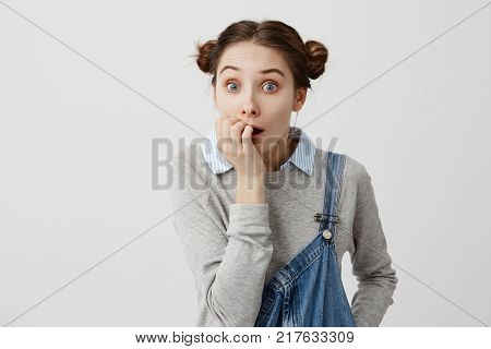 Schoolgirl with hair in double buns looking scared biting her nails in stress. Negative emotions of woman with eyes popping out being in trouble as she left her iron plugged. Human reactions