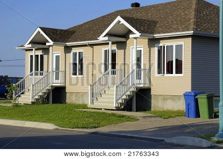 New construction and real estate: beige siding duplex house with recycling and garbage bins. poster