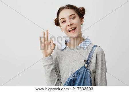 Closeup picture of good-looking woman showing alright with fingers laughing in rejoice. Adult female coach being glad for good results expressing happiness with gestures. Body language