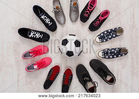 Bright and colorful sport shoes circle with ball top view. Set of different sneakers on wooden floor, copy space. Team game, competition concept