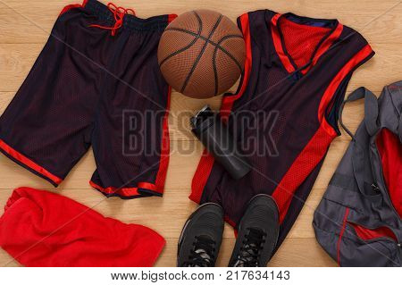 Basketball player outfit top view. Professional uniform, ball and sneakers on parquet floor