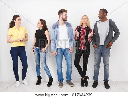 Multiethnic group of young adults standing on white background and discussing something,